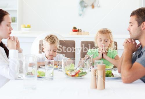 Portrait of a family praying together during the lunch