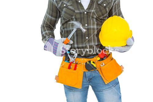 Manual worker wearing tool belt while holding hammer and helmet