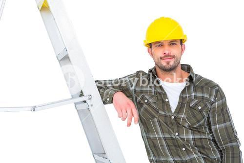 Smiling handyman in overalls leaning on ladder