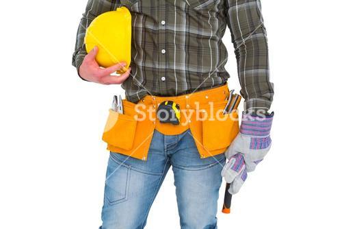 Manual worker wearing tool belt while holding gloves and helmet