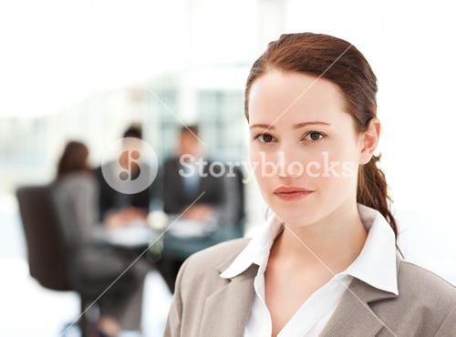 Charismatic businesswoman standing in the foreground while her team his working