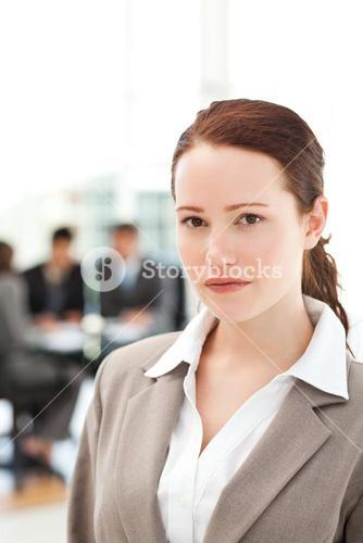 Serious businesswoman standing during a meeting with her team