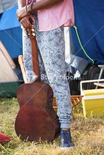 Hipster holding guitar at campsite
