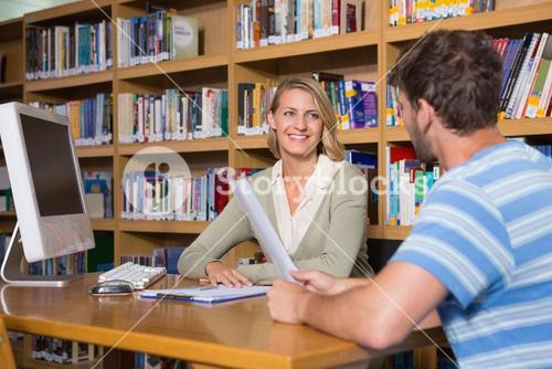 Student getting help from tutor in library