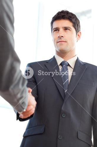 Below view of a serious businessman concluding a deal with a partner