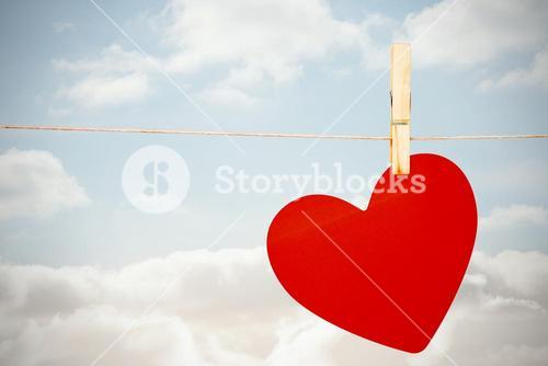 Composite image of heart hanging on line