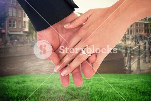 Composite image of close-up of bride and groom with hands together