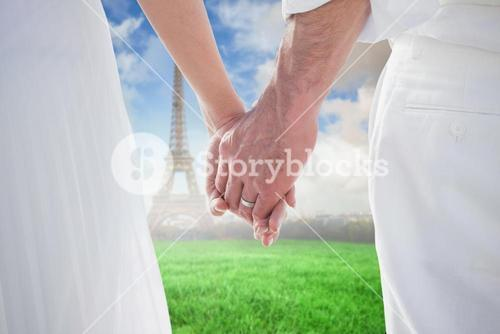 Composite image of bride and groom holding hands close up
