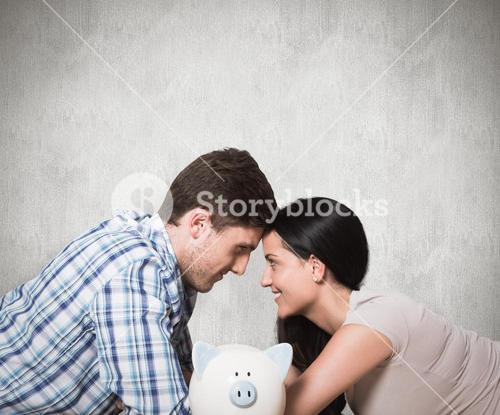 Composite image of young couple lying on floor smiling with piggy bank