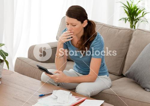 Anxious woman calculating her debts sitting in the livingroom