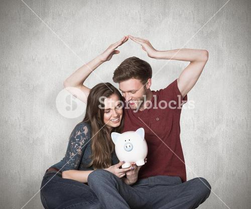 Composite image of couple sitting on floor with piggy bank