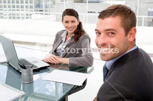 Happy businesspeople working together on a laptop during a meeting