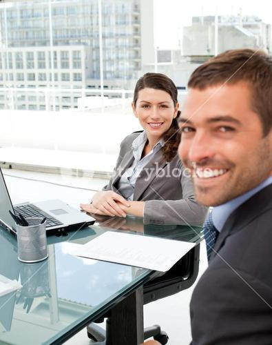 Two positive business people smiling at the camera