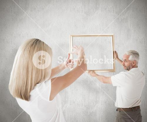 Composite image of couple hanging a frame together