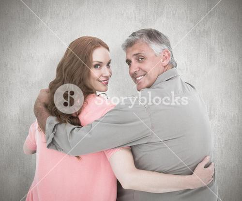 Composite image of casual couple standing arms around