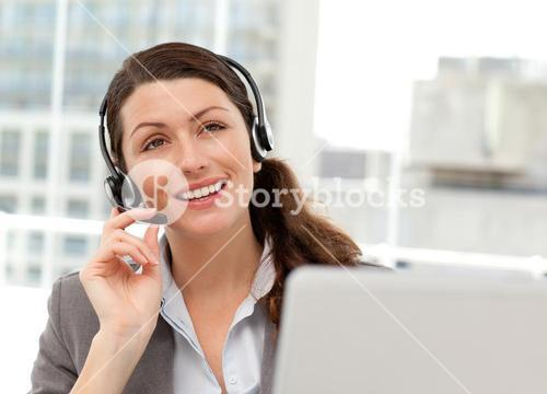 Thoughtful businesswoman talking on the phone while working on her computer