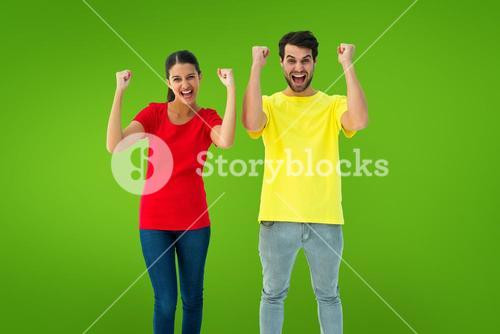 Composite image of excited couple cheering in red and yellow tshirts
