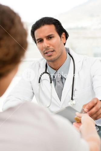 Serious doctor giving pills to his patient during an appointment