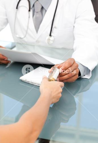 Close up of a doctor giving medicine to his patient during an appointment