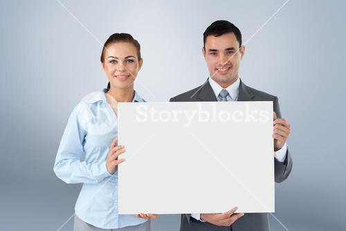 Composite image of business partners presenting sign