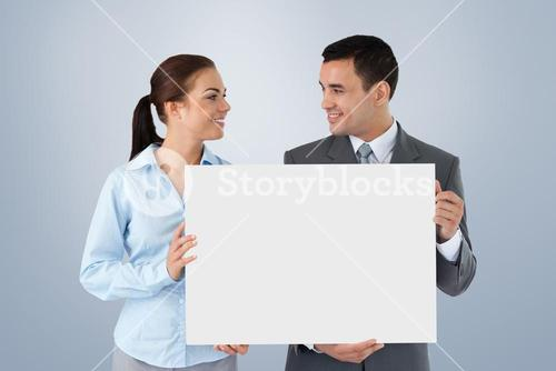 Composite image of young business partners presenting sign