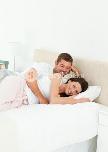 Cute couple lying together in their bedroom during a weekend