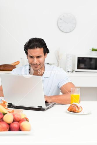 Charismatic hispanic man working on his laptop in the kitchen