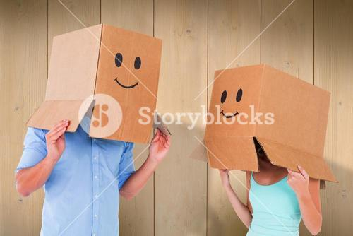 Composite image of couple wearing emoticon face boxes on their heads