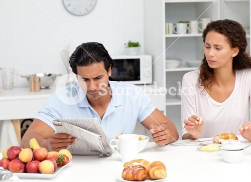 Concentrated couple reading the newspaper together during breakfast