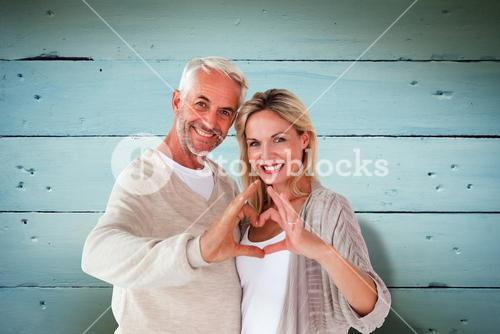Composite image of happy couple forming heart shape with hands