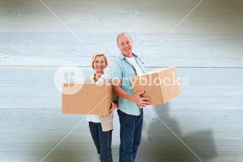 Composite image of older couple smiling at camera holding moving boxes
