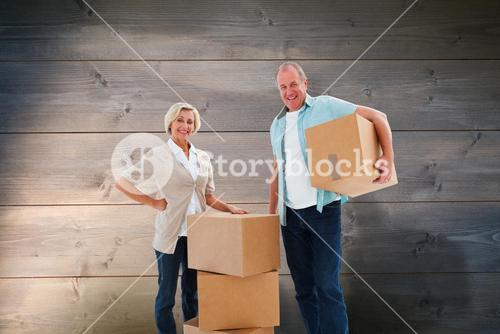 Composite image of older couple smiling at camera with moving boxes