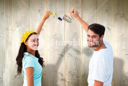 Composite image of happy young couple painting together