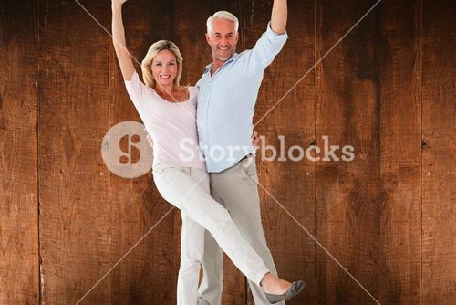 Composite image of smiling couple cheering at the camera