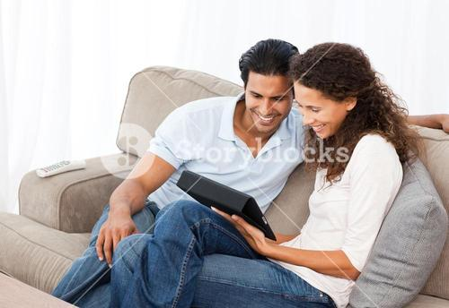 Lovely couple watching videos together sitting on their sofa