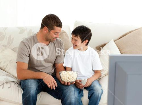 Father and son watching television while eating pop corn on the sofa