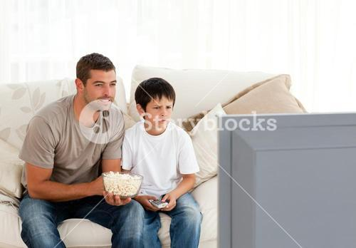 Concentrated father and son watching television while eating pop corn