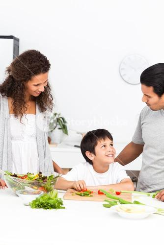 Happy family cutting vegetables together in the kitchen