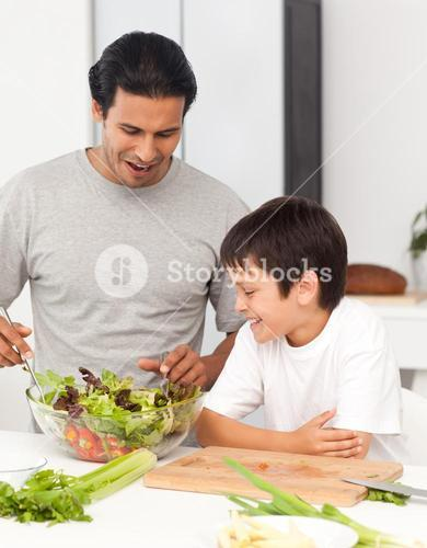 Handsome man preparing a salad with his son