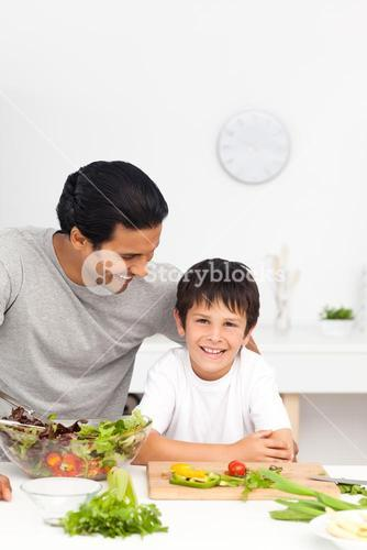 Happy father and son cutting vegetables together