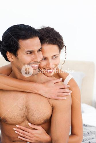 Passionate woman hugging her boyfriend sitting on their bed