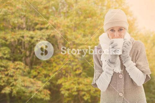 Composite image of woman in warm clothing holding mugs