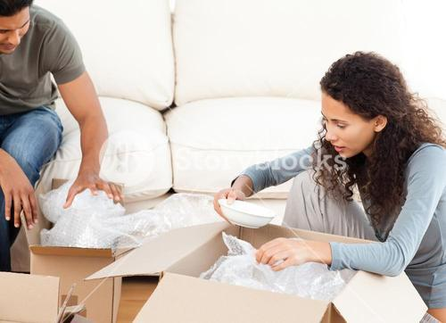 Happy woman packing glasses with her husband in the livingroom