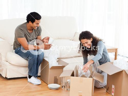 Happy couple packing glasses together in the livingroom