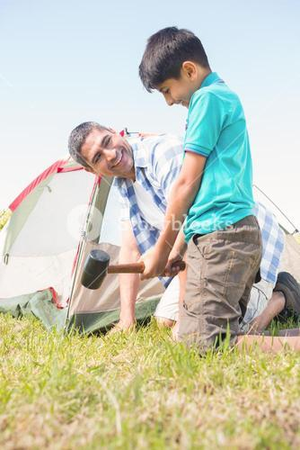 Father and son pitching their tent
