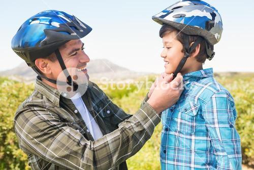 Father attaching his son cycling helmet