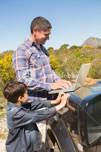 Father and son in the countryside using laptop