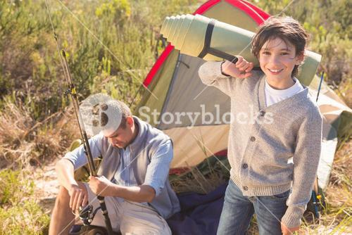 Father and son beside their tent in the countryside