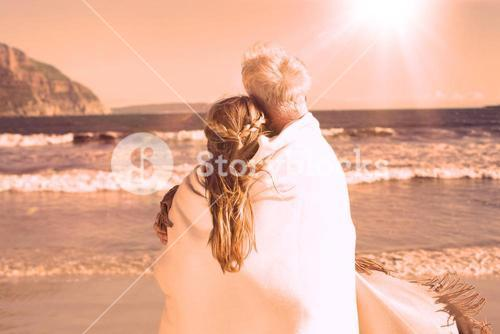 Couple wrapped up in blanket on the beach looking out to sea