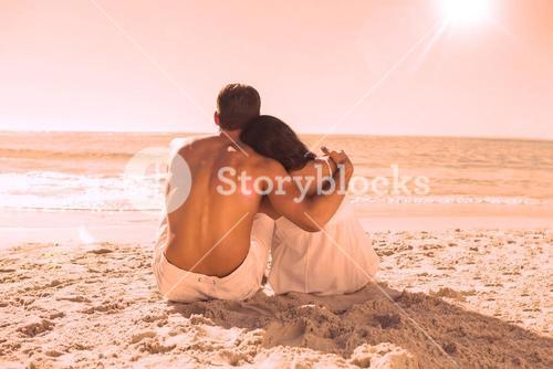 Couple sitting on the sand watching the sea